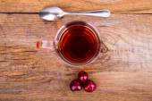 Cup of tea, spoon and sweet cherry on a wooden background — Stock Photo