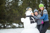 Happy smiling family with snowman — Stock Photo