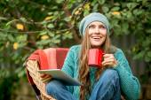 Beautiful woman with hot tea using tablet computer — Stock Photo