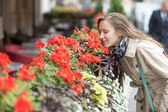 Beautiful young woman smell flowers — Stock Photo