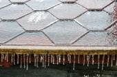 Icicles hanging down from a roof — Stock Photo