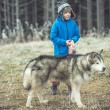 Funny small boy with his dog walking in autumn forest. motion — Stock Photo #58736219