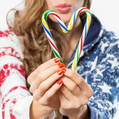 Closeup hands hold candy canes — Stock Photo