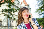 Young travel woman using cell phone talking on phone — Stock Photo