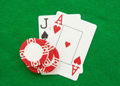 Blackjack hand with casino chip on green casino table — Stock Photo