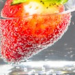 Strawberry in glass of mineral water. — Stock Photo #77608090