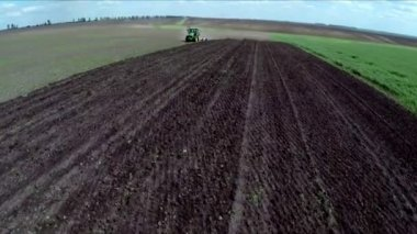 Tractor loosens the ground in the field. Aerial footage. Flying over a tractor in a field — Stock Video