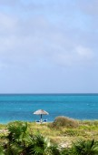 The view on the bright blue ocean with small umbrella at the sid — Stockfoto