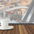 Coffee cup on wood table with fade out of shopping mall as backg — Stock Photo #74902267