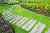 Stone walkway in flower garden — Stock Photo