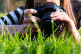 Woman taking a photo in grass — Stock Photo