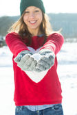 Girl playing with snow in red pullover and gloves — Stock Photo