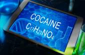 The chemical formula of  Cocaine on a tablet with test tubes — Stock Photo