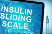 The words  Insulin sliding scale on a tablet with syringe — Stock Photo