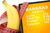 Tablet with Calories In banana  and measuring tape on white background. nutrition facts — Stock Photo