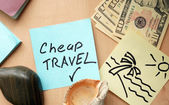 Cheap travel paper on a table with money — Stock Photo
