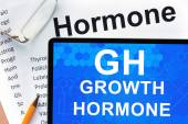 Papers with hormones list and tablet  with words  growth hormone (GH). — Stock Photo