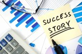Papers with graphs and words success story — Stock Photo