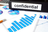 Folder with the label confidential and charts — Stock Photo