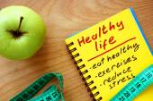 Notepad with healthy life guide, apple and measure tape — Stock Photo
