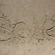 Sale. Word on the sand — Stock Photo #52520833