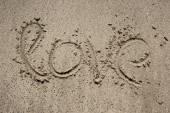 Inscription on sand near sea and waves. Love — Stock Photo