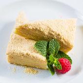 Tårta napoleon av smördeg med gräddfil på en tallrik. — Stockfoto