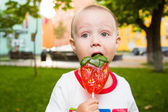 Young boy with colorful lollipop — Stock Photo