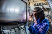 Man welding with reflection of sparks on visor. Hard job. — Stock Photo