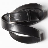 Black belt with a simple buckle on white background — Stock Photo