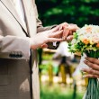 Mans hand putting a wedding ring on the brides finger — Stock Photo #64427019