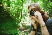 Closeup of young hipster man with digital camera outdoors. — Stock Photo