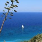 White sail in dark blue sea. Rhodes, Greece — Stock Photo #69246771