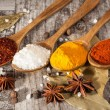 Spices. Spice in Wooden spoon. Herbs. Curry, Saffron, turmeric, cinnamon and other on a wooden rustic background. Pepper. Large collection of different spices and herbs. Salt, paprika. — Stock Photo #76900043