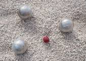 Metallic petanque balls and a small red jack — Stock Photo