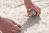 Hands picking up a petanque ball and the jack — Stock Photo