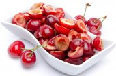 Cup of tasty pitted cherries with whole cherries — Stock Photo