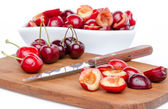 Composition with whole and pitted cherries — Stock Photo