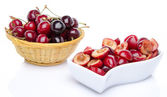 Cup of pitted cherries and whole cherries in a basket — Stock Photo