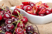 Cup of tasty pitted cherries and whole cherries — Stock Photo