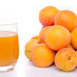 Glass of apricot juice next to a heap of apricots — Stock Photo #53929647