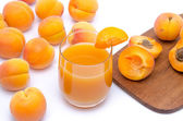 Glass of apricot juice with whole and sliced apricots — Foto Stock