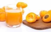 Verre de jus d'abricot avec des abricots entières et tranchées — Photo