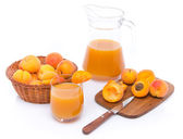 Glass and jug of apricot juice with a basket of apricots and sli — Stock Photo