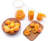 Jug and glasses of apricot juice with whole and sliced ripe apri — Stock Photo