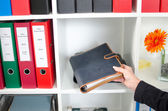 Businesswoman putting a diary in a shelf — Stock Photo