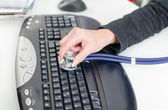 Woman's hand checking a keyboard with a stethoscope — Stok fotoğraf