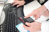 Workteam using a calculator and a computer — Stock Photo
