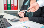 Workteam analyzing graphs and holding a pen — Stock Photo