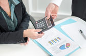 Workteam analyzing graphs and holding a calculator — Stock Photo